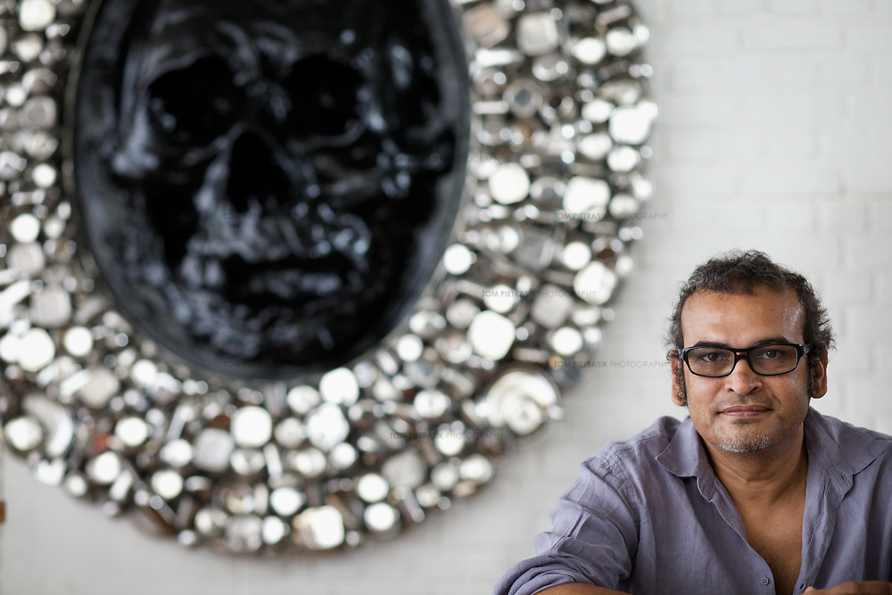 """Subodh Gupta, contemporary artist with one of his sculptures in his recently completed studio in Gurgaon, a satellite town of Delhi...Gupta's most celebrated sculptures are constructed from common domestic items including the steel pots and pans that are a feature every Indian home. Of the kitchen-ware that forms the basis of his work, Gupta says,..""""The poor, the middle class and the rich use it at home. In this country, how many people have the utensils but they starve because there is no food?""""..Gupta was brought up, one of six children, to a railway-worker father in a north Indian village. ..Gupta's work fetches such huge sums of money. Two versions of his Mind Shut Down, modeled on the human skull and constructed entirely of steel kitchen utensils recently sold for EUR1 million each...Photo: Tom Pietrasik.Gurgaon, Haryana. India. .June 26th 2009"""
