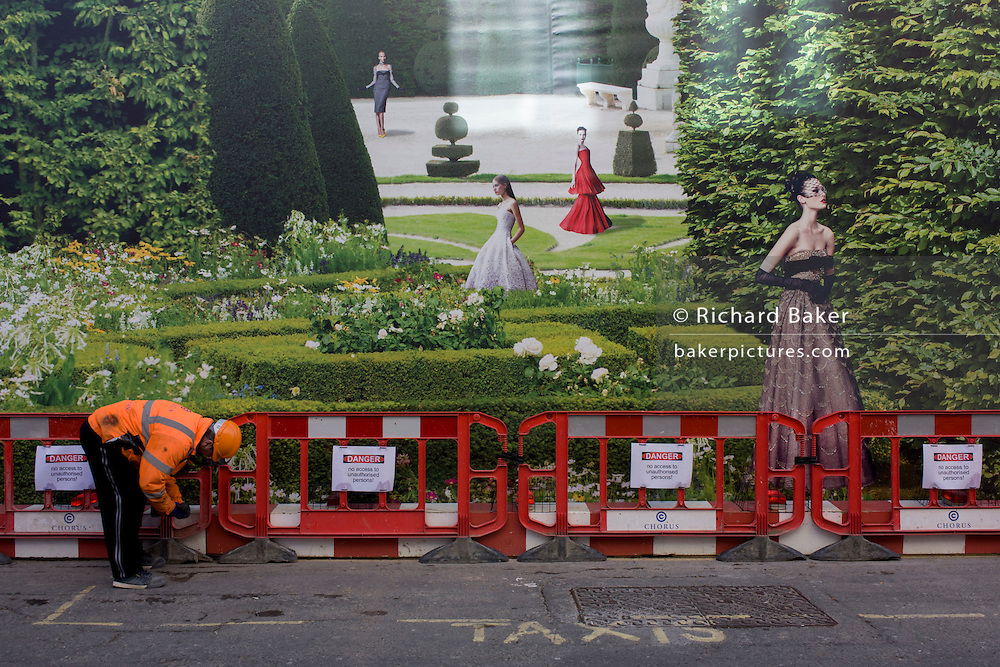 With a background of hanging hoarding media, a workman tidies up delivery barriers by a Dior shop being refurbished in central London.
