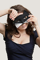 Portrait of a young woman wearing cat mask over gray background