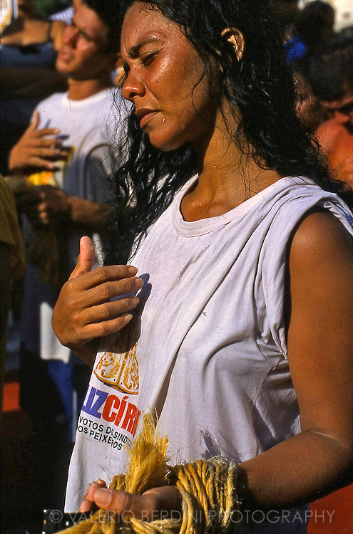 A woman and a man crossing themselves at the closing ceremony of Círio.