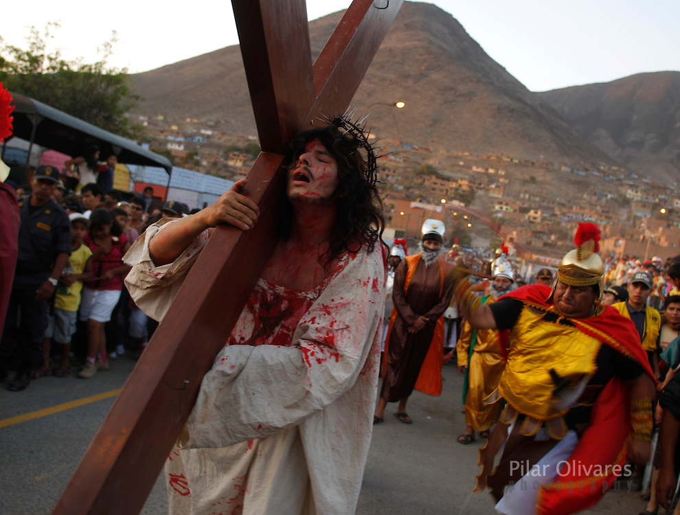 "An actor playing the role of Jesus Christ carries a cross as he is ""whipped"" in the re-enactment of the crucifixion of Jesus Christ on Good Friday during Holy Week on the outskirts of Lima April 2, 2010."