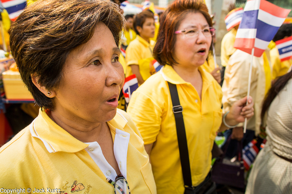 05 DECEMBER 2012 - BANGKOK, THAILAND:  Women sing the King's Anthem while they gather on the Royal Plaza Wednesday to see Bhumibol Adulyadej, the King of Thailand, before his public audience at the Mukkhadej balcony of the Ananta Samakhom Throne Hall. December 5 is a national holiday. It's also celebrated as Father's Day. Celebrations are being held across the country to mark the birthday of Bhumibol Adulyadej, the King of Thailand.   PHOTO BY JACK KURTZ
