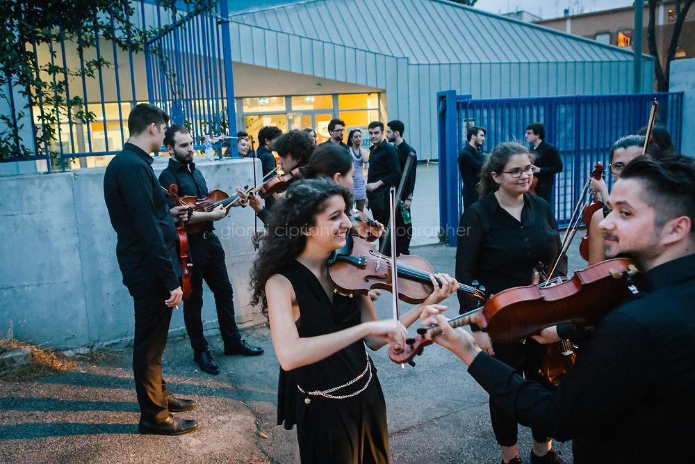 ROME, ITALY - 27 JUNE 2017: Musicians of the Youth Orchestra of the Teatro dell'Opera di Roma are seen here in the basement of the Aldo Fabrizi library (used as a changing room), before their performance of the &quot;Don Giovanni OperaCamion&quot;, an open-air opera performed on a truck,  in San Basilio, a suburb in Rome, Italy, on June 27th 2017.<br /> <br /> Director Fabio Cherstich&rsquo;s idae of an &ldquo;opera truck&rdquo; was conceived as a way of bringing the musical theatre to a new, mixed, non elitist public, and have it perceived as a moment of cultural sharing, intelligent entertainment and no longer as an inaccessible and costly event. The truck becomes a stage that goes from square to square with its orchestra and its company of singers in Rome. <br /> <br /> &ldquo;Don Giovanni Opera Camion&rdquo;, after &ldquo;Don Giovanni&rdquo; by Wolfgang Amadeus Mozart is a new production by the Teatro dell&rsquo;Opera di Roma, conceived and directed by Fabio Cherstich. Set, videos and costumes by Gianluigi Toccafondo. The Youth Orchestra of the Teatro dell&rsquo;Opera di Roma is conducted by Carlo Donadio.