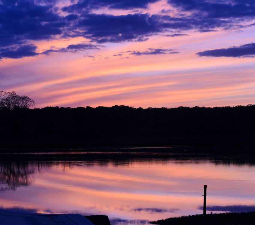 Trees and island in the backwaters, a tidal estuary, silhouetted against a cotton candy colored sky at sunset in the late spring, with reflections in the water, Niantic Connecticut, USA, May 2013.