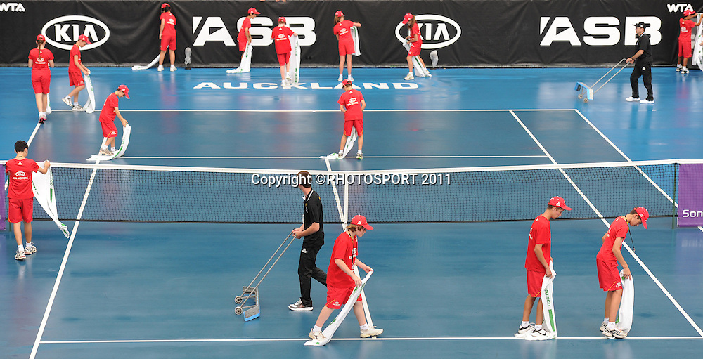 Volunteers and Kia sponsored ball boys and girls clear the water off center court on day 3 at the 2012 ASB Tennis Classic at the ASB tennis centre, Stanley st. Auckland. Wednesday 4  January 2012 Photo: Andrew Cornaga/photosport.co.nz