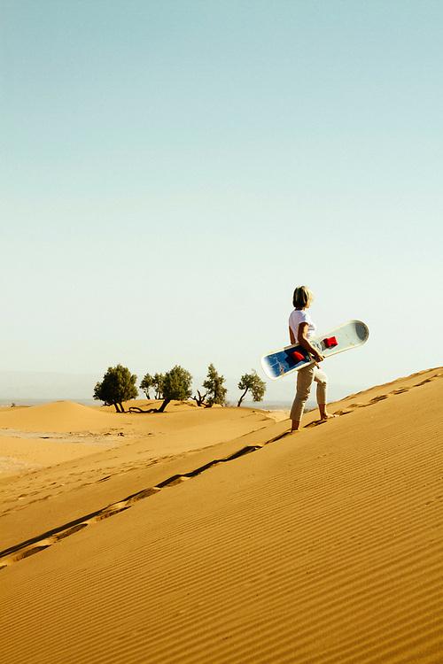 M'HAMID EL GHIZLANE, MOROCCO - 27th April 2014 - Tourist sandboarding in the desert sand dunes, beyond M'Hamid el Ghizlane, Erg Chigaga region of the Sahara desert, Southern Morocco.