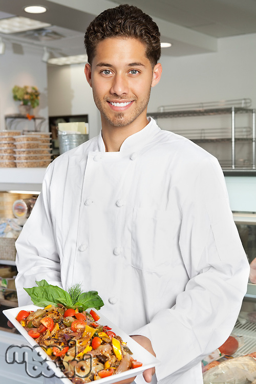 Portrait of young male chef holding chicken salad in serving dish