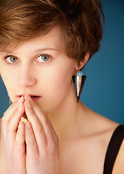 Close up of Teenage Girl with Hands in front of Mouth
