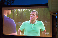 "Merrick, New York, USA. 11th June 2017.  On large TV screen, ""American Grit"" TV show contestant CHRIS EDOM (at right), 48, of Merrick, is host of Viewing Party for Season 2 premiere. Edom family's neighbors watched Episode 1 of the Fox network TV reality show on large screen in their backyard. Edom was the last contestant picked for a team."