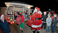 Santa Claus and his elves arrive via fire truck while dozens of families and friends gather to greet him during their annual Christmas party at the Wicwas Grange in Meredith Center Saturday evening.  (Karen Bobotas/for the Laconia Daily Sun)
