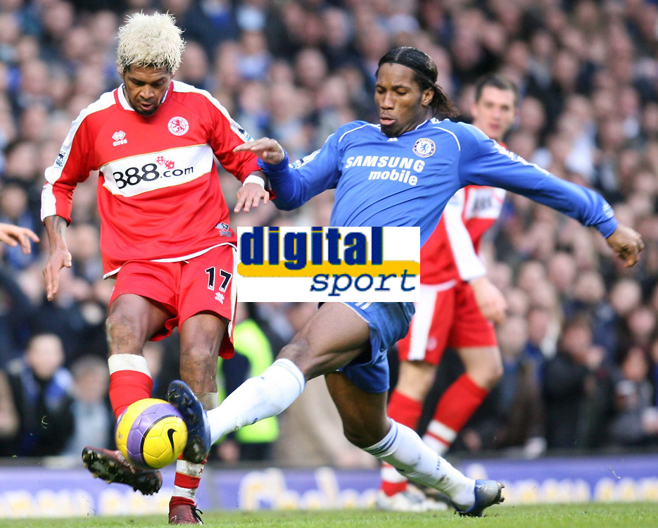 Drogba of Chelsea blocks the the clearence of Xavier of Middlesbrough