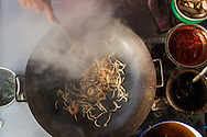 Frying char koay teow (rice noodles with shrimp, fish cake, bean sprout and egg). Air Itam, Penang, Malaysia
