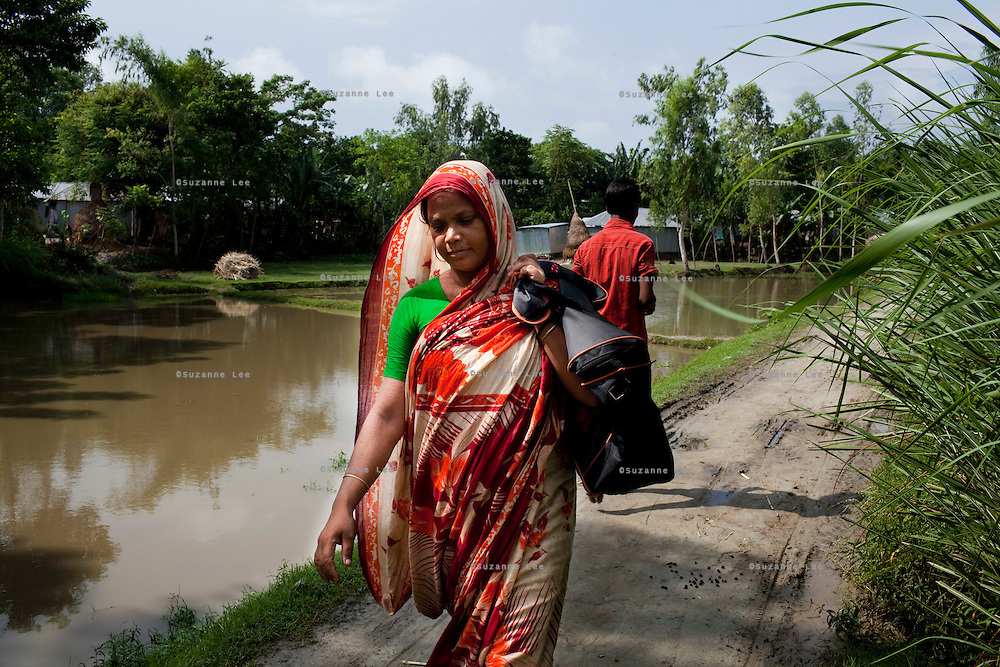 A widow, Rubi Begum, 40, walks through fields as she goes from door to door to sell her products in Ghagoa Villlage, Gobindagonj Upazila, Gaibandha, Bangladesh on 19th September 2011. Living alone after her husband's passing, she has now (since 2.5 years) found financial independence by working as a saleswoman, earning 3500 - 5000 Bangladeshi Taka per month. She is one of many rural Bangladeshi women trained by NGO CARE Bangladesh as part of their project on empowering women in this traditionally patriarchal society. Named 'Aparajitas', which means 'women who never accept defeat', these women are trained to sell products in their villages and others around them from door-to-door, bringing global products from brands such as BATA, Unilever and GDFL to the most remote of villages, and bringing social and financial empowerment to themselves.  Photo by Suzanne Lee for The Guardian
