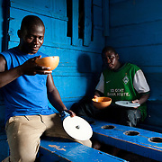 Francis (left) and Taidu arrived from Bolgatanga one month ago. In the mornings they pound fufu for a few cedis; they spend the day drinking pito in this bar; at night they sleep in a kiosk with five other young men. Agbogbloshie, Ghana.