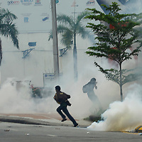 Malaysian protestors runs away from tear gas during a Bersih rally calling for electoral reforms  in Kuala Lumpur, Malaysia 9 July 2011.<br /> With national elections due by 2013, the opposition backed protest, Bersih is demanding reforms including measures to prevent vote-buying and fraud.