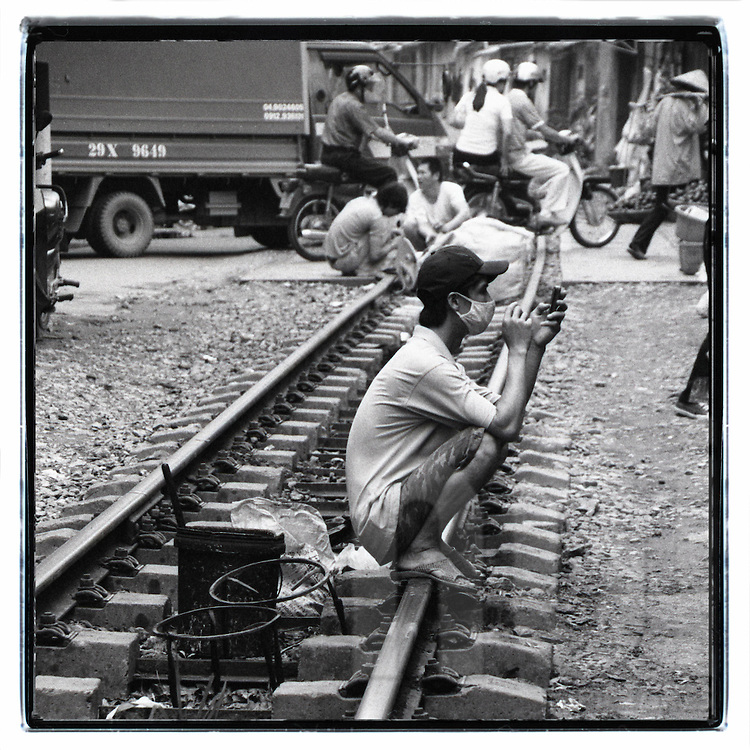 A Vietnamese man squats on the railways of Hanoi, Vietnam, Southeast Asia