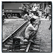A Vietnamese man squats on the railways of Hanoi, Vietnam, Southeast Asia