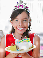 Portrait of girl (7-9) with piece of birthday cake on plate smiling