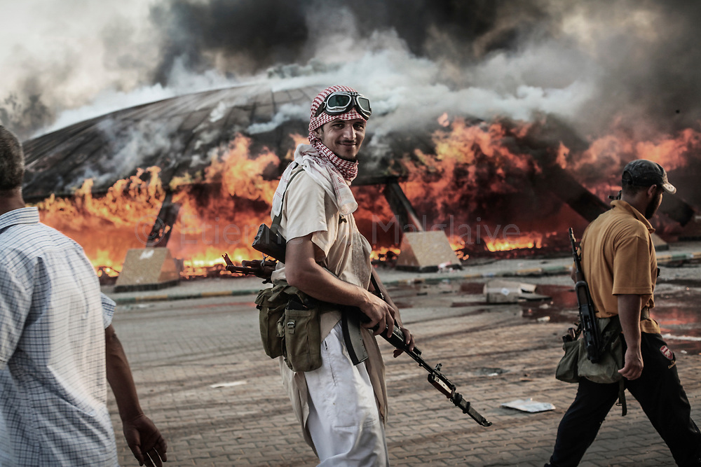 Libyan rebels attack Bab Al Azizyia,  Gadhafi's headquarters compound in Tripoli. After the compound was overrunned, fighters joined by civilians loot weapon depots inside the compound. 23 August 2011.