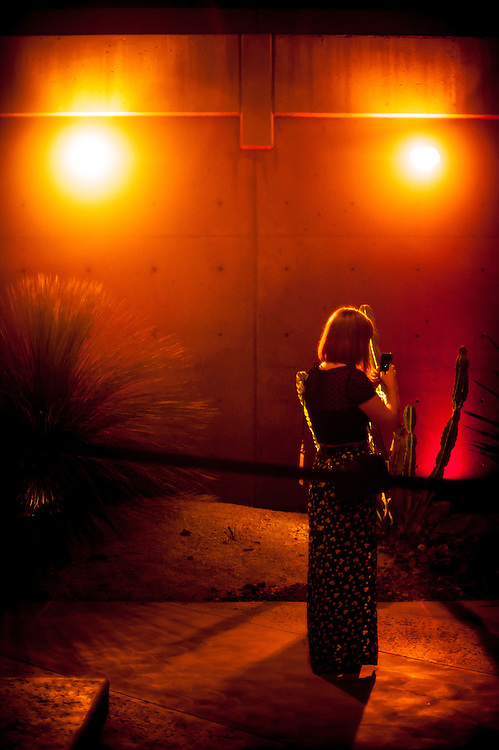 Young woman in a long skirt looking at her smart phone in Palm Springs, California. It is evening with a very warm glow.