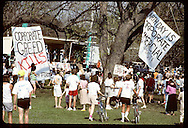 Banners deriding corporate sponsors of Earth Day hang over fair crowd; Forest Park in St. Louis. Missouri