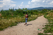 "A bodypainted boy is running on a path towards river ""Bodva"" to cool down on a tropical day. From about 800 inhabitants of the segregated settlement 'Budulovska Street' (2014) are roughly 392 children up to the age of 16 years."