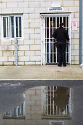 An officer opens the gate into Beaufort House, a skill development unit for enhanced prisoners. Part of HMP/YOI Portland, a resettlement prison with a capacity for 530 prisoners.Dorset, United Kingdom.
