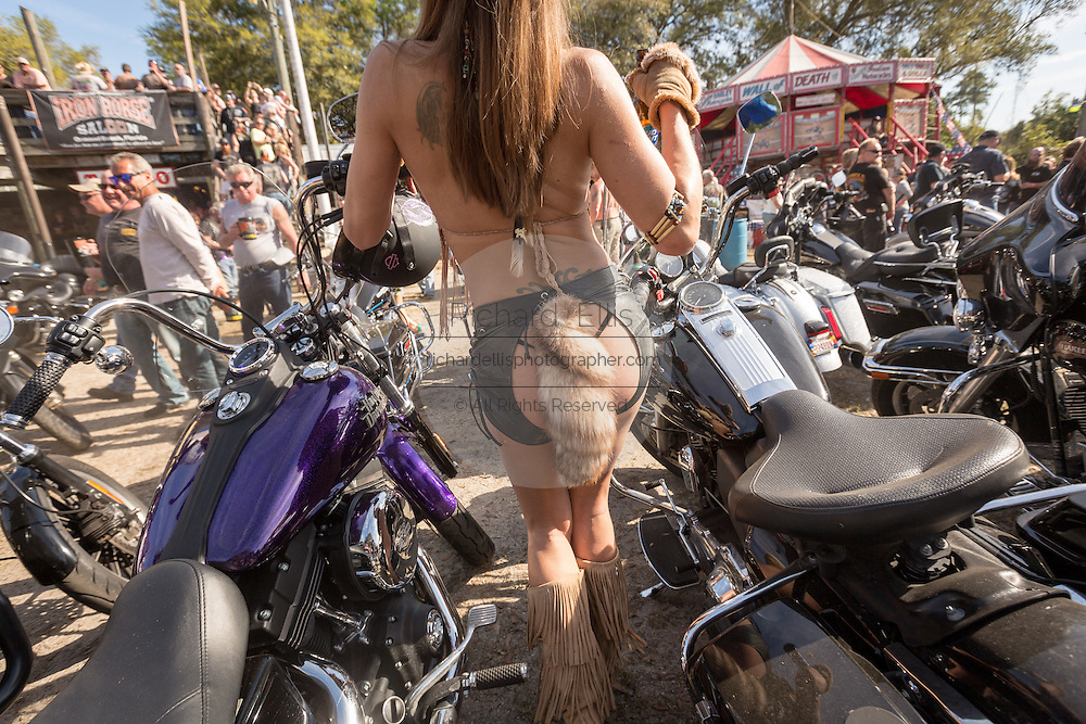 A scantly dressed waitress weaves past parked Harley-Davidson motorbikes at the Iron Horse Saloon during the 74th Annual Daytona Bike Week March 8, 2015 in Ormond Beach, Florida. More than 500,000 bikers and spectators gather for the week long event, the largest motorcycle rally in America.