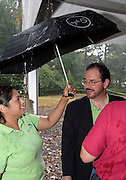 Nina Basu Howard, general counsel for Innerarbor Trust holds an umbrella for Michael McCall during the heavy rains.