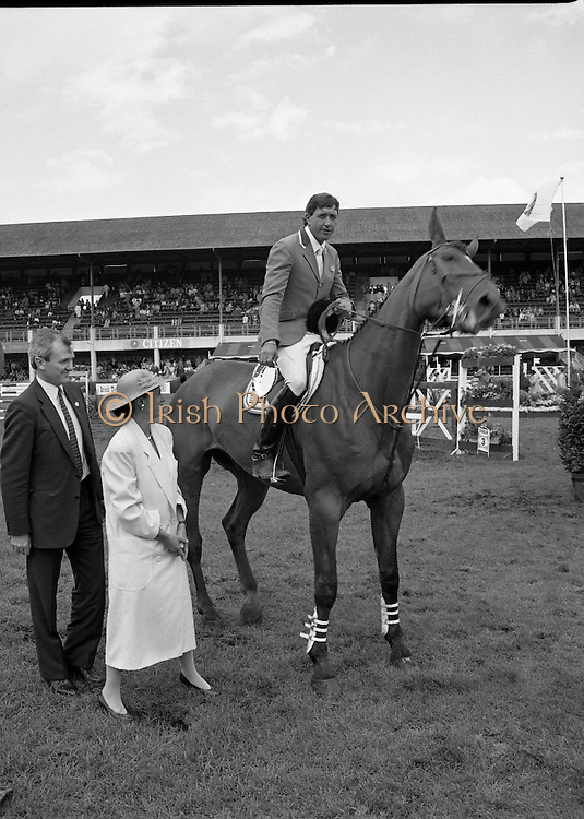 Shell Sponsored Events At The Dublin Horse Show.(R39).1986..07.08.1986..08.07.1986..7th August 1986..At the Horse Show Shell sponsored both the Speed and Power competition and The Puissance..The Speed and Power event was won by Hap Hanson riding 'Gambrinus'. The Puissance was shared by Capt John Ledingham (Irl) on 'Kilcoltrim' and Nick Skelton (GB) on 'Raffles Apollo' who both cleared the high wall at 7feet...Picture shows the winner of the Shell Power and Speed event Hap Hanson (USA) on 'Gambrinus' receiving his trophy from Mrs Pamela Witherington and Mr John Witherington, Managing Director, Irish Shell limited.