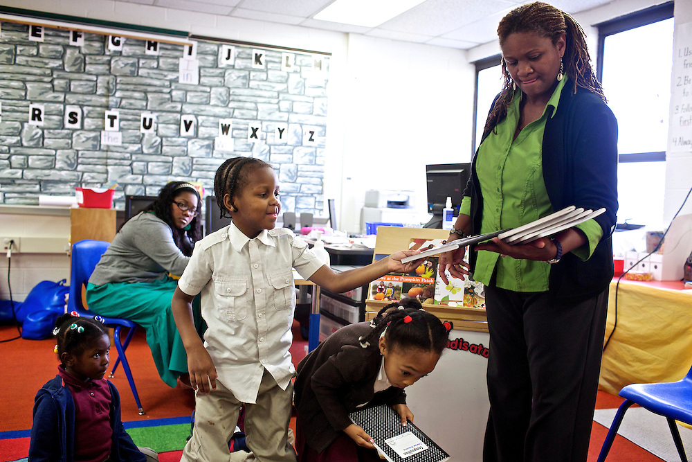 "Pre-kindergarten students at Calvin Rodwell Elementary School No. 256 in Baltimore, MD, including James Manley III, 4, grab their journals from their teacher Erika Parker, right, to write and draw what they think they'll see at a farm after they read the book ""A Day at the Pumpkin Patch,"" a non-fiction children's book about visiting a farm. The book was part of a ""Common Core"" reading and learning unit, which aims to follow up non-fiction reading with learning in the field. The day after the children read the book about the farm, they visited Summers Farm in Frederick, MD."