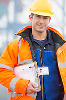 Portrait of confident mid adult man with clipboard in shipping yard