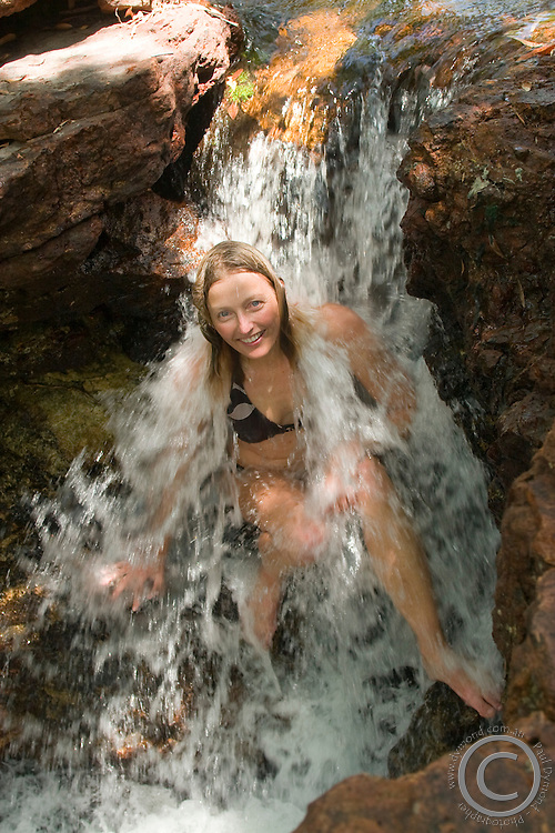 A young woman enjoys a refreshing swim in a small waterfall in the heart of the Aurukun Wetlands in remote Cape York, far northern Queensland, Australia.