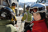 A girl, 10-12, of mixed race, looks over her shoulder as she carries her skis while walking with her family through Whistler Village, BC, on a sunny winter day.
