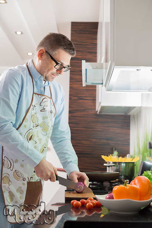 Mid-adult man cutting vegetables at kitchen counter
