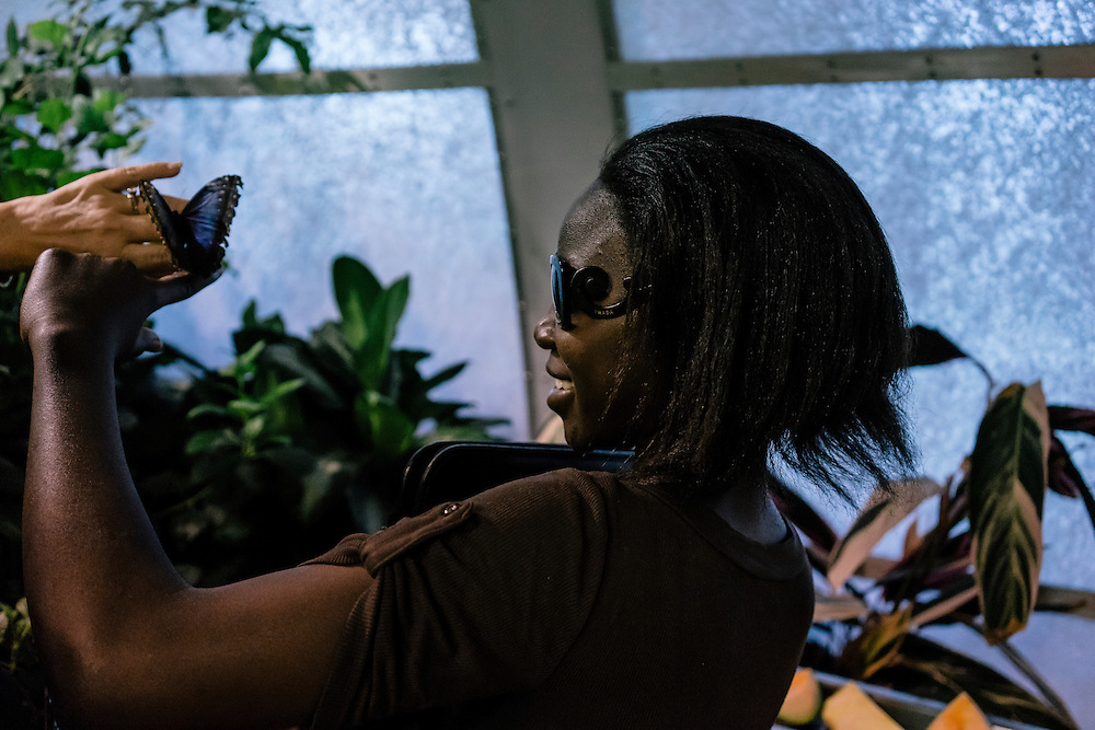 Lily, who escaped from Boko Haram during the kidnapping of almost 300 girls in Nigeria, has a butterfly land on her hand while touring the butterfly pavilion at the National Museum of Natural History in Washington, D.C. with Deanna Gelak, human development expert. Gelak is providing Lily and other girls who escaped, a summer of english and enrichment programs.