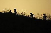 """Oct 20, 2006; Walnut, CA, USA; Silhouettes of runners in the Division V boys sweepstakes race cresting """"Reservoir Hill,"""" the last major incline in the 2.91-mile race, in the 59th Mt. San Antonio College Cross Country Invitational."""
