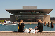 Two young women sit by the waterside in view of the Copenhagen Opera House whilst a boat coasts by.