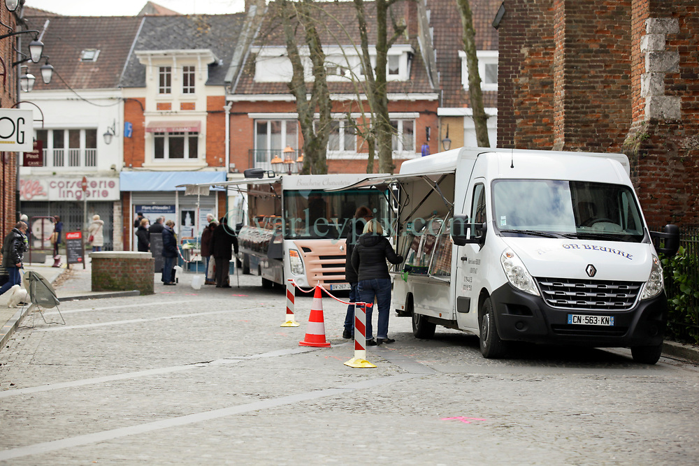 02 April 2020. Hesdin, Pas de Calais, France. <br /> Coronavirus - COVID-19 in Northern France.<br /> <br /> Easing restrictions on local markets. For the first time since government restrictions came into force, the main market in Hesdin has been permitted to re-open. The historical town has hosted a usually vibrant and bustling market since the middle ages. With stall holders limited and many suffering huge financial losses, those selling food today were happy to be back to work despite the ongoing risks posed by coronavirus.<br /> <br /> Shoppers, many wearing masks were mostly maintaining their social distancing with people happy to be out and able to meet and talk with other people. A lot of shoppers were elderly people who have been trapped in their homes for weeks. One shopper complained of 'la misère,' - the misery of this virus and being stuck in her home. <br /> <br /> Anyone leaving their home must carry with them an 'attestation,' in a effect a self administered permit to allow them out of the house. If stopped by the police, one must produce a valid permit along with identification papers. Failure to do so is punishable with heavy fines. Movement in France has been heavily restricted by the government and today's market re-opening was a brief return to normalcy for many able to escape the confines of their homes.<br /> <br /> Photo©; Charlie Varley/varleypix.com