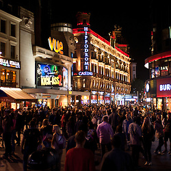 People enjoy the Friday nightlife in Leicester Square in London on August 16, 2013. Leicester Sq is a pedestrianised square in the West End and is the prime location in London for world leading film premières.