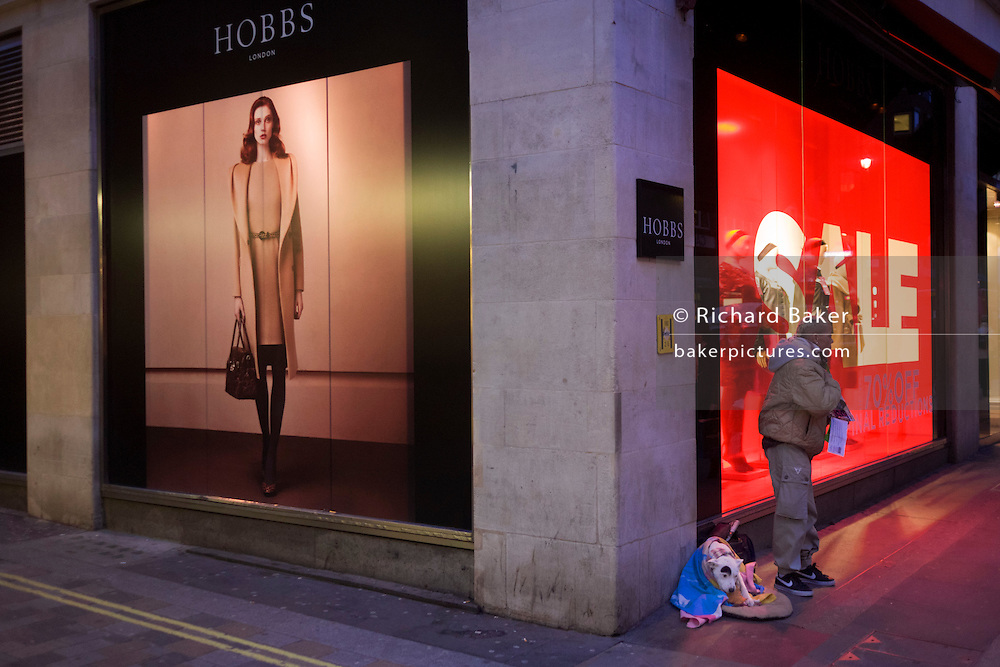 A Big Issue seller awaits custom with her pet dog on pavement outside clothing shop Hobbs in central London.