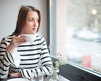Thoughtful young woman looking out from window while drinking coffee in cafe