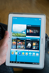 Man using Samsung Galaxy Note 10.1 tablet computer running Android operating system and showing large home screen