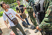 "25 OCTOBER 2012 - TAK BAI, NARATHIWAT, THAILAND: Thai soldiers talk to Muslim men in Tak Bai, Thailand. The ""Tak Bai Incident"" took place on Oct. 25 in Tak Bai, Narathiwat, Thailand during the Muslim insurgency in southern Thailand. On that day, a crowd gathered to protest the arrest of local residents. Police made hundreds of arrests during the protest and transported the arrested to Pattani, about two hours away, in another province. They were transported in locked trucks and more than 80 people suffocated en route. This enraged local Muslims and shocked people across Thailand. No one in the Thai army accepted responsibility for the deaths and no one was ever charged. In the past, the anniversary of the incident was marked by protests and bombings. This year it was quiet. More than 5,000 people have been killed and over 9,000 hurt in more than 11,000 incidents, or about 3.5 a day, in Thailand's three southernmost provinces and four districts of Songkhla since the insurgent violence erupted in January 2004, according to Deep South Watch, an independent research organization that monitors violence in Thailand's deep south region that borders Malaysia.   PHOTO BY JACK KURTZ"