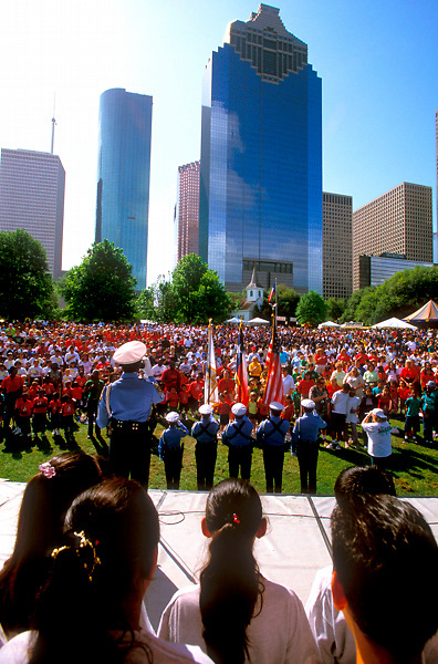 Stock photo of a large crowd in Sam Houston Park as police officers raise flags