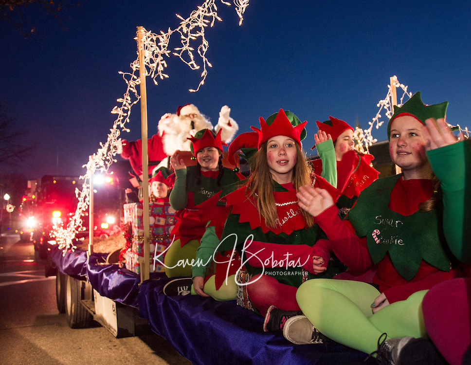 Santa's Elves wave to the crowds lining Main Street during the annual holiday parade followed by the tree lighting in Veteran's Square on Sunday evening.  (Karen Bobotas/for the Laconia Daily Sun)