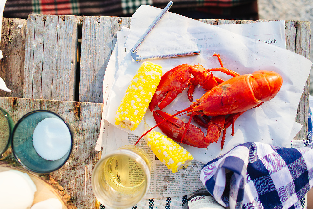Lobster and corncobs outdoors.