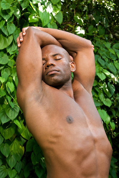 A young african american stretching while practicing yoga in a natural environment.