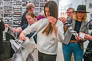 "Portland, Oregon, USA. 26 FEB, 2018. Gallery goers help in shredding the photographer Robert Frank's work printed on newsprint at Blue Sky Gallery in Portland, Oregon, USA. The work was destroyed in a ""Destruction Dance"" performance defacing the photographs with ink and mutilation with scissors, knives and even ice skates  at the end of it's run. The destruction was Frank's protest regarding today's greed in the global art market."