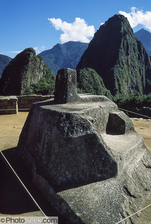 "The four-sided Intihuatana (Hitching Post of the Sun) ritual stone sculpture was likely the most sacred place in Machu Picchu, a magnificent Inca archeological site in the Cordillera Vilcabamba, Andes mountains, Peru, South America. The name Intihuatana (coined perhaps by Hiram Bingham) is derived from the Quechua language: inti means ""sun""; huata- is a Spanish spelling of wata-, the verb root ""to tie or hitch (up)""; and the -na suffix derives nouns for tools or places. Scholars dispute various theoretical uses of Intihuatana such as a sacrificial altar, as a temple aligned with the surrounding mountains and their resident apus (gods), as a solar observatory (but unlikely as a sundial), or simply as an abstract art work. The mysterious Intihuatana is an important huaca (or waqa), a revered object, in Quechua language. The stone is at 13°9'48"" South latitude. Machu Picchu was built around 1450 AD as an estate for the Inca emperor Pachacuti (14381472). Spaniards passed in the river valley below but never discovered Machu Picchu during their conquest of the Incas 1532-1572. The outside world was unaware of the ""Lost City of the Incas"" until revealed by American historian Hiram Bingham in 1911. Machu Picchu perches at 2430 meters elevation (7970 feet) on a well defended ridge 450 meters (1480 ft) above a loop of the Urubamba/Vilcanota River (Sacred Valley of the Incas). UNESCO honored the Historic Sanctuary of Machu Picchu on the World Heritage List in 1983."